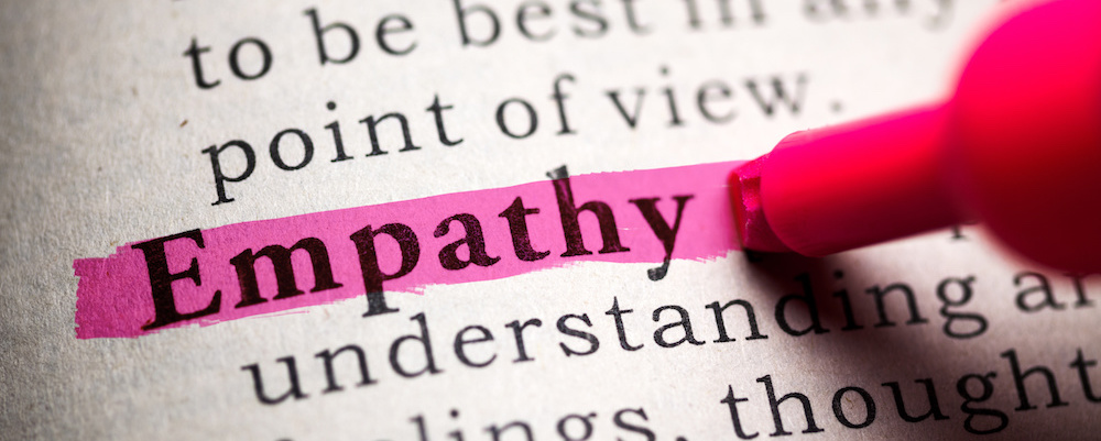 the word empathy highlighted pink in a dictionary